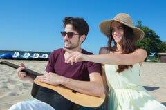 Jeune homme avec la guitare et l'amie sur la plage Image stock