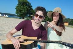 Jeune homme avec la guitare et l'amie sur la plage Photographie stock libre de droits