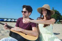 Jeune homme avec la guitare et l'amie sur la plage Photographie stock