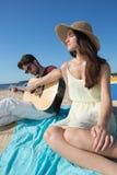 Jeune homme avec la guitare et l'amie sur la plage Images stock