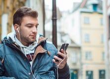 Jeune homme avec la musique de écoute de téléphone portable et d'écouteurs Photo libre de droits