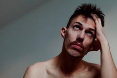 Jeune homme avec la pensée de moustache photographie stock libre de droits