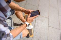 Jeune homme avec la planche à roulettes utilisant le téléphone Image stock
