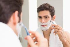 Jeune homme avec la réflexion rasant dans la salle de bains Photos stock