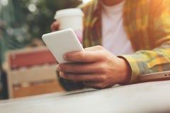 Jeune homme avec la tasse du café et du smartphone à disposition se reposant en café de rue, causant avec des amis Photo libre de droits