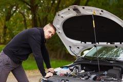 Jeune homme avec la voiture cassée photo stock