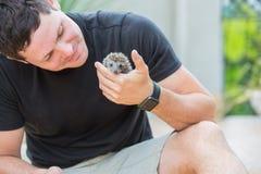 Jeune homme avec le bébé de hérisson Images libres de droits