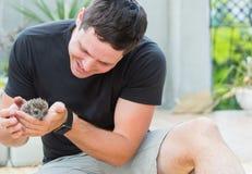 Jeune homme avec le bébé de hérisson Photo libre de droits