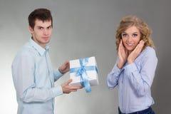 Jeune homme avec le cadeau et l'amie étonnée Image libre de droits