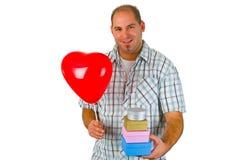 Jeune homme avec le cadre rouge de ballon et de cadeau Images stock