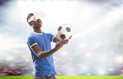 Jeune homme avec le casque de réalité virtuelle ou les verres 3d au-dessus du terrain de football sur le fond de stade Photo stock