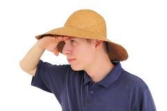 Jeune homme avec le chapeau de paille observant à la distance Images libres de droits