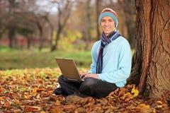 Jeune homme avec le chapeau et l'écharpe travaillant sur l'ordinateur portatif Photographie stock