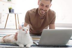 Jeune homme avec le chat et l'ordinateur portable mignons Photos libres de droits