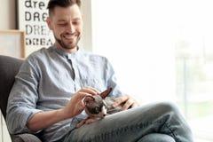 Jeune homme avec le chat mignon à la maison Image stock