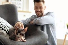 Jeune homme avec le chat mignon Photos stock