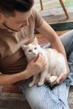 Jeune homme avec le chat mignon se reposant sur le plancher Image libre de droits