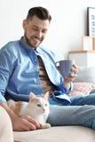 Jeune homme avec le chat mignon sur le sofa à la maison Photo stock