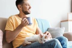 Jeune homme avec le chat mignon sur le sofa Photographie stock libre de droits