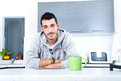 Jeune homme avec le comprimé dans la cuisine photos stock