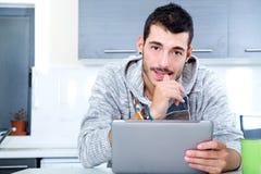 Jeune homme avec le comprimé dans la cuisine images stock