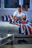 Jeune homme avec le comprimé dans le lit image libre de droits