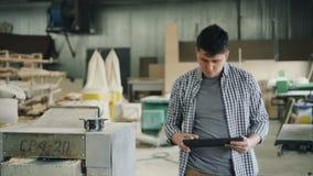 Jeune homme avec le comprimé marchant dans l'atelier en bois regardant le bois de construction et l'équipement banque de vidéos