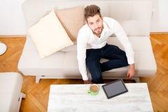 Jeune homme avec le comprimé sur le divan Photo libre de droits