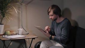 Jeune homme avec le contact de PC de comprimé dans un café ayant une certaine tasse de café Photo stock