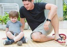 Jeune homme avec le fils jouant avec le bébé de hérisson Image libre de droits