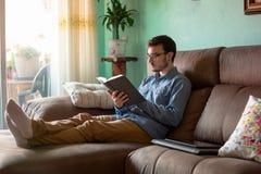 Jeune homme avec le livre sur le sofa ? la maison photo stock