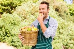 Jeune homme avec le panier mangeant la pomme photo libre de droits