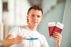 Jeune homme avec le petit avion dans l'aéroport attendant son vol photographie stock