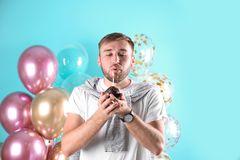 Jeune homme avec le petit pain d'anniversaire et les ballons à air image libre de droits