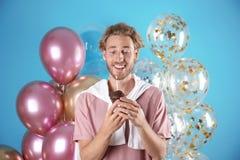Jeune homme avec le petit pain d'anniversaire et les ballons à air photos libres de droits