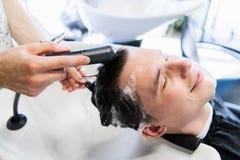 Jeune homme avec le problème de perte des cheveux obtenant ses cheveux lavés avant de recevoir l'injection image libre de droits