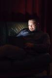 Jeune homme avec le repos d'ordinateur portable sur le divan dans la chambre noire Photo libre de droits