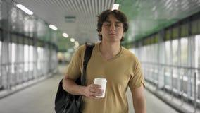 Jeune homme avec le sac marchant avec du café clips vidéos