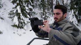 Jeune homme avec le smartphone sur le télésiège clips vidéos