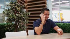 Jeune homme avec le symbolisme d'arc-en-ciel dans un café, parlant sur le téléphone et le sourire banque de vidéos