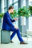 Jeune homme avec le téléphone intelligent dans l'aéroport Homme caucasien avec le téléphone portable à l'aéroport tout en attenda Photo libre de droits