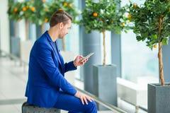 Jeune homme avec le téléphone portable à l'aéroport tout en attendant l'embarquement Veste de port de costume de jeune garçon occ Photographie stock