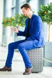 Jeune homme avec le téléphone portable dans l'embarquement de attente d'aéroport international Photo libre de droits
