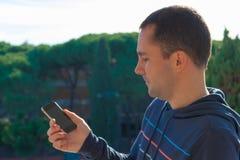 Jeune homme avec le téléphone portable sur le fond d'arbres, extérieur Image stock