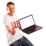 Jeune homme avec le T-shirt et l'ordinateur portable de ` de vente de ` Photo libre de droits