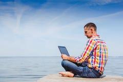 Jeune homme avec le travail d'ordinateur portable extérieur photographie stock libre de droits