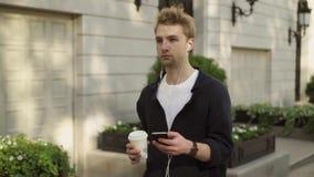 Jeune homme avec les écouteurs et le café marchant dans la rue banque de vidéos