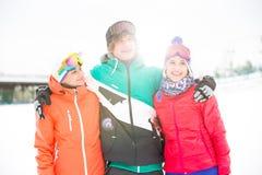 Jeune homme avec les amis féminins tenant le bras autour dans la neige Photos libres de droits