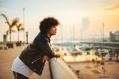 Jeune homme avec les cheveux Afro appréciant la vue du coucher du soleil dans la ville image libre de droits