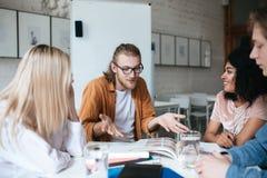 Jeune homme avec les cheveux blonds et barbe expliquant avec émotion quelque chose à ses amis Groupe de personnes s'asseyant au Photos libres de droits